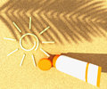 Tube of sunscreen on beach sand with a painted sun with the shadow a palm branch Stock Image
