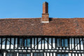 Tudor house details brick chimney above the red tailed roof of the timber framed Stock Photos