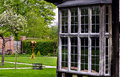 Tudor house exterior detail built in 1590 detail of window and garden outdoors Blakesley hall closeup Royalty Free Stock Photo
