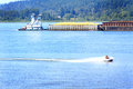 Tug and barge traffic a boat pushing a in the lane in the columbia river gorge past a jet ski river recreation common daily scene Stock Photo