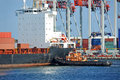 Tugboat assisting bulk cargo ship container to harbor quayside Stock Images