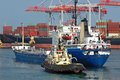 Tugboat assisting bulk cargo ship to harbor quayside Stock Image