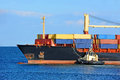 Tugboat assisting container cargo ship to harbor quayside Royalty Free Stock Photography
