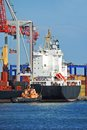 Tugboat assisting container cargo ship to harbor quayside Royalty Free Stock Photos