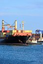 Tugboat assisting container cargo ship to harbor quayside Stock Image