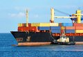 Tugboat assisting container cargo ship to harbor quayside Stock Photos