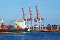 Tugboat assisting container cargo ship to harbor quayside Stock Images