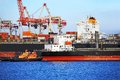 Tugboat assisting container cargo ship to harbor quayside Royalty Free Stock Photo