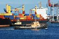 Tugboat assisting container cargo ship to harbor quayside Stock Photo