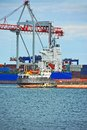 Tugboat assisting container cargo ship to harbor quayside Stock Photography