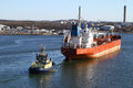 Tugboat with cargo ship a blue assisting a large red oil tanker Stock Photos