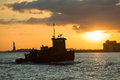 Tugboat heads towards new york from liberty island at sunset Royalty Free Stock Photo