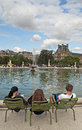 Tuileries garden tourists sit next to s fountain paris france Royalty Free Stock Image