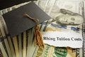 Tuition headlines graduation cap on cash with rising costs newspaper headline Royalty Free Stock Photos