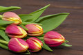Tulips bouquet red and yellow on wooden dark background Royalty Free Stock Images