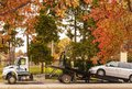 stock image of  Tulsa USA Tow truck with operator making adjustments a van is loaded on trailer on street on a beautiful and colorful
