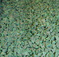 Tumbling media green material in triangle shapes used to polish new machine parts Royalty Free Stock Photo