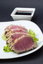 Tuna fillet on white dish with salad and soy sauce black background Stock Photography
