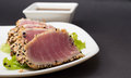 Tuna fillet on white dish with salad and soy sauce black background Stock Photo
