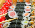 Tuna maki single roll in chopsticks on sushi made dish background Stock Photo