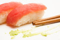 Tuna nigiri sushi two pieces of wasabi and chopsticks in close up Royalty Free Stock Photo