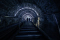 The tunnel the descent into the mine flight of stairs people are going up steps their silhouettes arched ceiling a long narrow Royalty Free Stock Photo