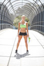 Through the tunnel a female athlete standing under a pedestrian walkway with a cage over top Stock Images