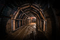 Tunnel in old coal mine reinforced with wood corridor modern tracks and elements of internal infrastructure visible Stock Images