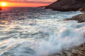 Turbulent sea under a fiery orange sunset or sunrise with waves breaking on rocky shoreline sending up clouds of white spray Stock Photos
