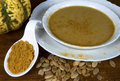 Tureen of curried pumpkin soup bowl curry in white bowl with curry powder squash and seeds Stock Image