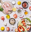 Turkey breast On a cutting board with herbs different fruits and vegetables Cucumbers mushrooms tomato salad pepper lemon in a Royalty Free Stock Photo