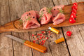 Turkey breast wooden board with pieces of raw meat decorated with cherry tomatoes rosemary juniper berries and pomegranate Royalty Free Stock Image