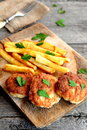 Turkey meat cutlets served with potatoes and garnished with parsley on a wooden board. Rustic stile. Closeup