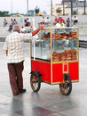 Turkish bagel street vendor istanbul september sells bagels at eminonu square on september in istanbul drinking tea with simit Royalty Free Stock Images