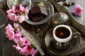 Turkish coffee chocolate and branch with pink flowers a on an old table Royalty Free Stock Images