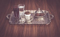 Turkish coffee served with water, sherbet and cookies on traditional copper serving set