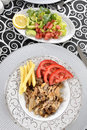 Turkish kebab with french fries and tomatoes on dish Royalty Free Stock Photography