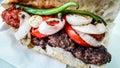 Turkish Kofte Ekmek / Meatball Sandwich with tomatoes, onion and green pepper. Royalty Free Stock Photo