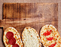 Turkish pita bread on a wooden cutting board. Mini pizzas Royalty Free Stock Photo