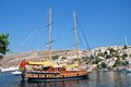 Turkish sailing boat symi a flagged moored in yialos harbour on the greek island of on june the neoclassical buildings of the town Stock Photos