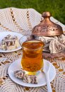 Turkish tea in a glass Cup and marble halva on a table with a handmade tablecloth and candy maker on a Sunny day Royalty Free Stock Photo