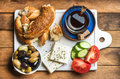 Turkish traditional breakfast with feta cheese, vegetables, olives, simit bagel and black tea on white ceramic board