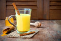 Turmeric golden milk latte with cinnamon sticks and honey. Detox liver fat burner, immune boosting, anti inflammatory drink