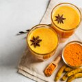 Turmeric smoothie in glass with ingredients, powder, ginger and spice on white