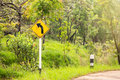 Turn left sign on the way between hill in Thailand. Royalty Free Stock Photo