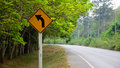 Turn left warning sign on a curve road Royalty Free Stock Image