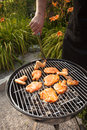 Turning chicken wings and steaks on a barbeque grill. Royalty Free Stock Photo