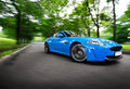 Turning fast blue luxury coupe park road Royalty Free Stock Photography