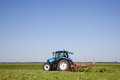 Turning grass for drying with tractor in dutch meadow Stock Photos