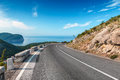 Turning mountain highway with blue sky and sea on a background Stock Photography